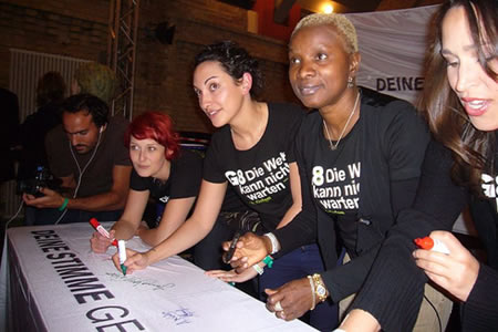 """At Oxfam Deutschland's """"Sister Soul"""" concert ahead of the G8 Summit, stars Angelique Kidjo, Laura Lopez Castro, Diane and China from Pink Martini, sign the """"Your Voice Against Poverty"""" banner"""