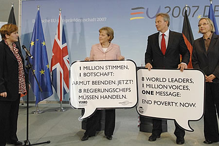 "British Prime Minister Tony Blair, German Chancellor Angela Merkel, Claudia Warning (R) and Ulla Mikota (L), both members of the NGO VENRO, hold a banner that reads ""8 world leaders, 1 million voices, one message: end poverty now"" during a press conference on June 03, 2007 in Berlin, Germany. The two politicians were given signatures that were part of the campaign ""Global Call to Action against Poverty"". (Photo by Miguel Villagran/Getty Images)."