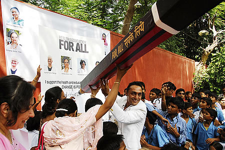 "Children dressed up as doctors, nurses and teachers help actor Rahul Bose sign Oxfam's giant ""For All"" Petition calling for universal health and education."